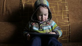 Little boy in hood browse tablet pc stock video