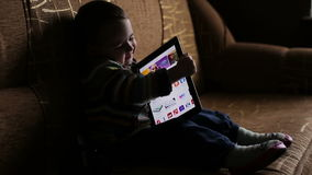 Little boy in hood browse tablet pc stock video footage