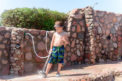 Little boy hosing off his shoes and feet Royalty Free Stock Photography