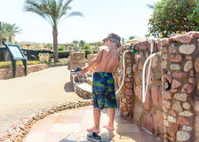Little boy hosing off his shoes and feet Royalty Free Stock Photos