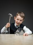 Little boy with house model and hammer Royalty Free Stock Photography