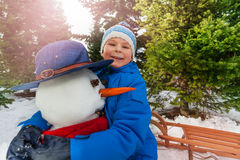 Little boy hug snowman in the park and smile Royalty Free Stock Image