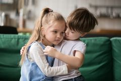 Little boy brother consoling and supporting upset girl embracing. Little boy hugging consoling upset girl sitting on sofa, kid brother embracing sad sister stock image