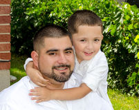 Little boy hugging dad. A sweet portrait of a little boy hugging his father Stock Image