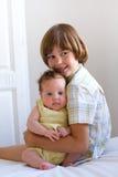 Little boy hugging and enjoying his newborn sister Stock Photography