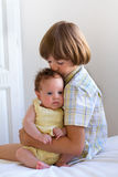 Little boy hugging and enjoying his newborn sister. Little boy hugging and enjoying his newborn cute sister royalty free stock photos