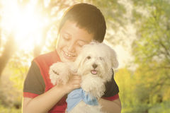 Little boy hugging his dog on the park Stock Photo