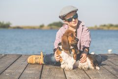 Little boy hugging his dog by the river royalty free stock photos