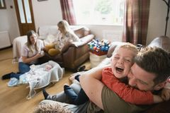 Little Boy Hugging His Father. Family with two children and their grandmother sitting in the living room on sofas. They are relaxing, watching the tv and talking stock photography
