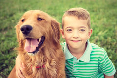 Little boy hugging his golden retriever pet dog Stock Image