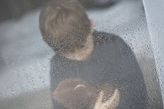 The little boy is hugging his teddy bear. Selective focus. Standing behind wet from rain window glass. Rainy Day. Loneliness and waiting concept Royalty Free Stock Image