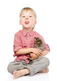 Little boy hugging a kitten showing his tongue. is Stock Photography