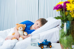 Little boy hugging teddy bear and lying in hospital bed Stock Image