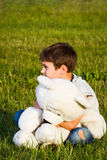 Little boy hugging teddy bear while sitting on the grass. stock image