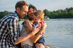 Little boy hugs his dad and mom and they smiling in outdoors. Near a river at sunset. Happy family stock photos