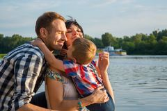Little boy hugs his dad and mom and they smiling in outdoors nea. R a river at sunset. Happy family royalty free stock photos