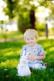 Little boy hunting for easter egg in spring garden on Easter day Stock Photos