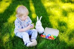 Little boy hunting for easter egg in spring garden on Easter day Stock Images