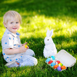 Little boy hunting for easter egg in spring garden on Easter day Royalty Free Stock Photo