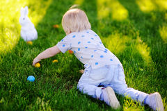 Little boy hunting for easter egg in spring garden on Easter day Royalty Free Stock Photos