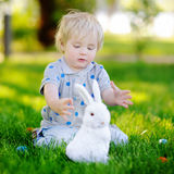 Little boy hunting for easter egg in spring garden on Easter day Royalty Free Stock Images