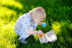 Little boy hunting for easter egg in spring garden on Easter day Royalty Free Stock Photography