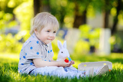 Little boy hunting for easter egg in spring garden on Easter day Royalty Free Stock Image