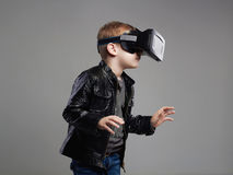 Little Boy i virtuell verklighetexponeringsglas som spelar leken roliga ungar Fotografering för Bildbyråer