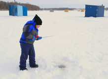 Little Boy Ice Fishing. Young boy ice fishing in winter Stock Photo