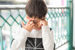 Little boy ichy his eyes with crying outdoor sadness face Stock Photo