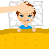 Little boy ill in bed with thermometer in mouth Royalty Free Stock Photography