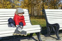 Little boy imitates adults - dresses roller skates. On a park bench in autumn Stock Image