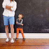 Little boy imitating his father's pose. Indoor shot of little boy and his father standing with hands folded against black wall. Father and son looking at each stock images