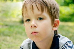 Little boy indifferently looking away Stock Images