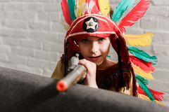 Little boy in indigenous costume with toy gun playing. At home stock photo