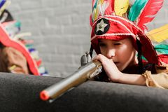 Little boy in indigenous costume with toy gun playing. At home royalty free stock photo