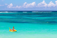 Little boy on an inflatable boat on tropical beach Stock Photos