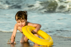 A little boy with an inflatable circle splashing into the sea. In the background there are sea waves stock photography