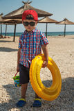 A little boy with an inflatable circle for swimming in glasses on the beach near the sea. Umbrellas against the sun and sand in the background stock image