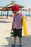 A little boy with an inflatable circle for swimming in glasses on the beach near the sea. Umbrellas against the sun and sand in the background stock photos