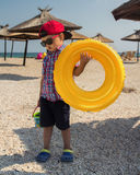 A little boy with an inflatable circle for swimming in glasses on the beach near the sea. Umbrellas against the sun and sand in the background stock images