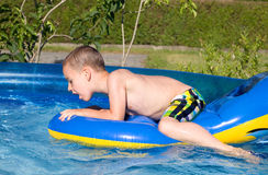 Little boy with inflatable in the pool Stock Image