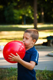Little boy inflate big red  balloon in park Stock Photo