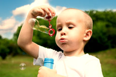 Little boy inflates soap bubbles. In the park. Image with Instagram-like filter Stock Image