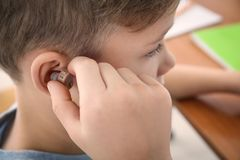 Little boy inserting hearing aid,. Closeup royalty free stock image