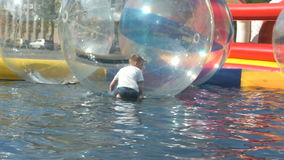 Little boy inside a big inflatable ball in water stock video footage