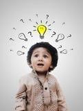 Little Boy intelligente adorabile che pensa - punti interrogativi Fotografia Stock