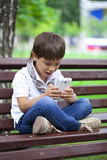 Little boy intently playing games on smartphone Royalty Free Stock Image