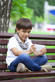 Little boy intently playing games on smartphone Stock Photo