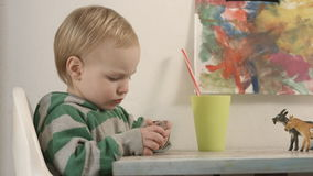 A little boy is interested in playing on the phone. stock footage